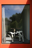 A sculpture by Jean-Baptiste Galmiche of a black and white cow gazes out of the upstairs floor-to-ceiling window which has a painted orange surround