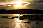 Idaho, North, Coeur d' Alene Lake. A boat heads to dock beneath a summer sunset on Lake Coeur d' Alene.