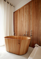 A smooth birchwood bath tub designed by Matteo Thun et Antonio Rodriguez is placed infront of a wall lined with exotic wood by Olivier Tourenc in this unusual bathroom