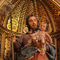 Statue, possibly of St Joseph holding the Christ child by Jose de Mora, 18th century, in the Jesuit Church of Saints Justus and Pastor of Alcala, built 1575 on the site of a mosque in Granada, Andalusia, Southern Spain. Saints Justus and Pastor were 4th century schoolboy christian martyrs, who were killed for their faith under the persecution of the christians by the Roman emperor Diocletian. Granada was listed as a UNESCO World Heritage Site in 1984. Picture by Manuel Cohen