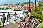 Benches on the waterfront with a view of Gravedona in the background, a town at the northern end of Lake Como, Italy
