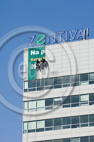 """BRATISLAVA - SLOVAKIA 11. MARCH 2007 -- Two workers in the top of a high building of the company Zentiva! hanging up a advertising banner in the outskirts of Bratislava  -- PHOTO: GORM K. GAARE / EUP & IMAGES..This image is delivered according to terms set out in """"Terms - Prices & Terms"""". (Please see www.eup-images.com for more details)"""