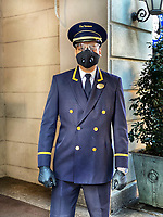 New York City, New York, Coronavirus in New York. Doormen are considered essential workers and suit up for the job to protect against COVID19.  They continue to intercept food deliveries, packages and keep the buildings safe.