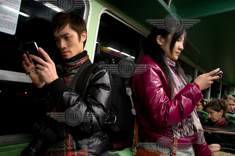 Japanese tourists check their mobile phones during a nightime boat ride.