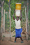 A woman struggles to stand as she balances two buckets full of water on her head at a well in Bunj, South Sudan.