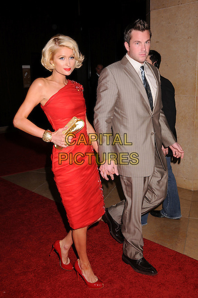 PARIS HILTON & DOUG REINHARDT.An Evening With Women: Celebrating Art, Music & Equality held at the Beverly Hilton Hotel, Beverly Hills, CA, USA..April 24th, 2009.full length red dress gold clutch bag beaded one shoulder bracelet cuff grey gray pinstripe suit tie couple patent shoes .CAP/ADM/BP.©Byron Purvis/AdMedia/Capital Pictures.
