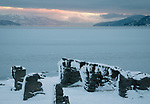 Idaho, North, Bonner County, Sandpoint. Low winter water levels on Lake Pend Oreille reveal remains of stuctures at dawn.