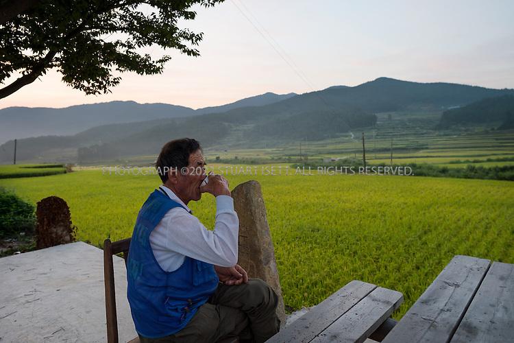 9/11/13 -- Cheongsando Island, Jeonnam Province (Jeollanam-do), South Korea<br /> <br /> A farmer has morning coffee at sun rise next to rice fields on Cheongsando Island.<br /> <br /> Photograph by Stuart Isett<br /> &copy;2013 Stuart Isett. All rights reserved.