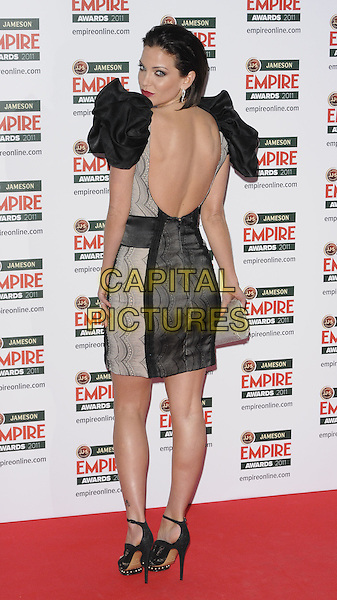 SARAH HARDING.The Empire Film Awards, Grosvenor House Hotel, Park Lane, London, England..March 27th, 2011.full length black dress sheer backless looking over shoulder ruffle shoulder .CAP/CAN.©Can Nguyen/Capital Pictures.