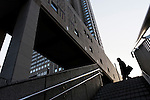 A salaryman or male office worker carrying a briefcase walks past part of the Tokyo metropolitan Government building in Shinjuku, Tokyo, Japan. Friday, January 21st 2011