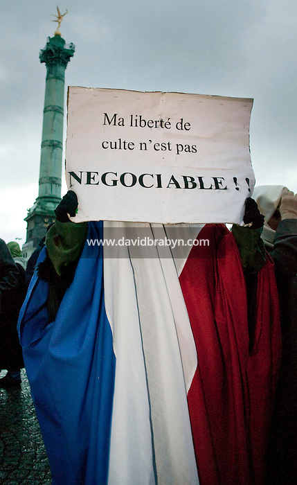 "A muslim woman wearing a full head-to-toe chador made out of the French red-white-and-blue flag holds up a sign in French that reads ""my freedom of religion is not negotiable"" during a street protest held in Paris, France, 21 December 2003, against a law that plans to restrict the wearing of veils in public schools."
