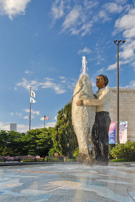 A statue and fountain of a man holding a fish spouts water on a summer day in front of the Shedd Aquarium in the Museum Campus on Chicago's Lakefront