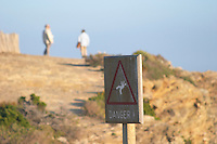 A sign saying Danger and warning for falling off the cliffs and two persons in the background standing on the edge of the cliff on the St Pierre des Embies island outside Sanary Le Brusc Six Fours Var Cote d'Azur France