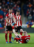 Enda Stevens and John Fleck help Oli McBurnie of Sheffield Utd with cramp during the Premier League match at Bramall Lane, Sheffield. Picture date: 9th February 2020. Picture credit should read: Simon Bellis/Sportimage