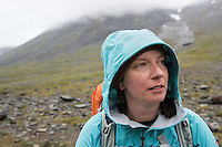 Portrait of female hiker in rain with hood on in mountain landscape, Kungsleden trail, Lapland, Sweden