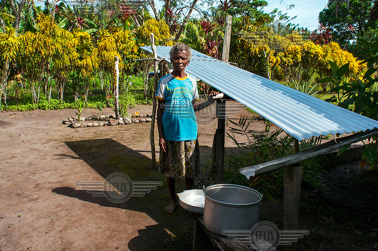 Grace Tovoba stands next to her rain water catchment made from corrugated iron.