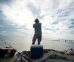 Mauricio Ensales casts his line off of a rock jetty by the Bay Bridge at Sandy Point State Park on a Saturday morning.