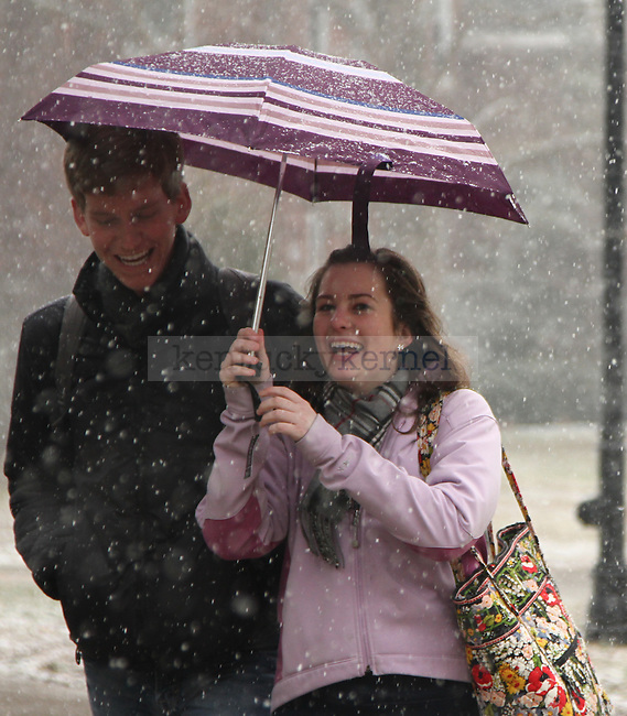 Art history sophomore Carly Dannenmueller and Economics sophomore Ryan Knott laugh while finding shelter under Dannenmueller's umbrella between classes near Whitehall, Thursday. Photo by Brandon Goodwin   Staff
