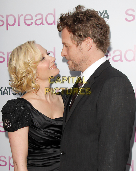 "ANNE HECHE & JAMES TUPPER .at The Anchor Bay Films screening of ""Spread""  held at The Arclight Theatre in Hollywood, California, USA,.August 3rd 2009.                                                                  .half length dress black shoulder pads cap sleeves silver earrings brooch silk satin ruched suit tie profile looking at each other .CAP/DVS.©Debbie VanStory/RockinExposures/Capital Pictures"