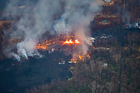 lava emanating from Pu'u O'o on Kilauea Volcano, erupts from fissures in Leilani Estates, spreading out rapidly into the subdivision and combusting methane generated from burning vegetation, near Pahoa, Puna, Big Island, Hawaii, USA