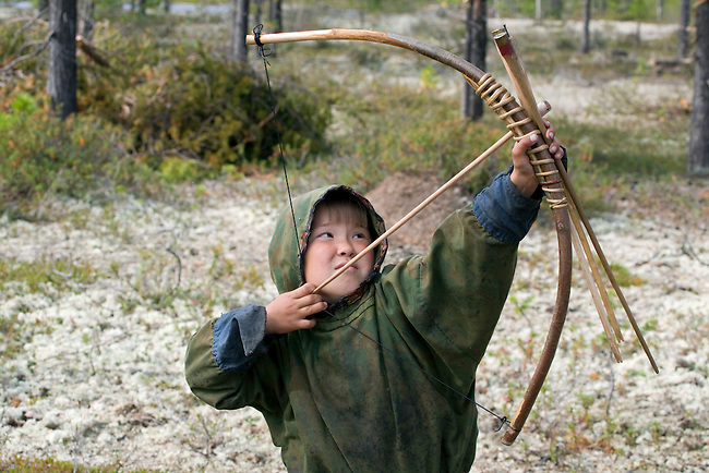 Dima Piak, a Forest Nenets boy, with his bow and arrow out hunting birds in the summer. Purovsky Region, Yamal, Western Siberia, Russia