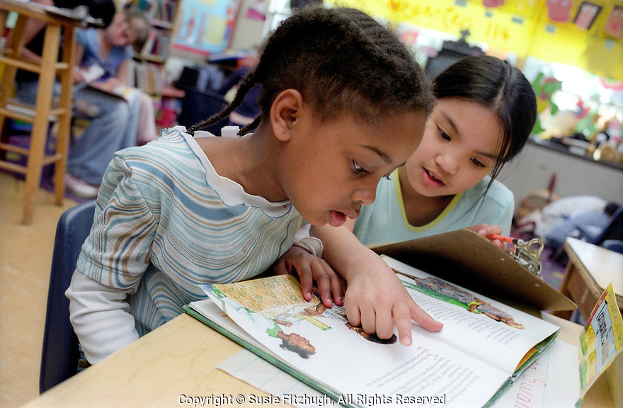 At reading time, two friends work together to read a book.