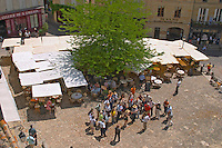 The main town square in Saint Emilion with Cafes with outside seating terrasse with parasols and a group of visiting tourists with a guide Saint Emilion Village Bordeaux Gironde Aquitaine France