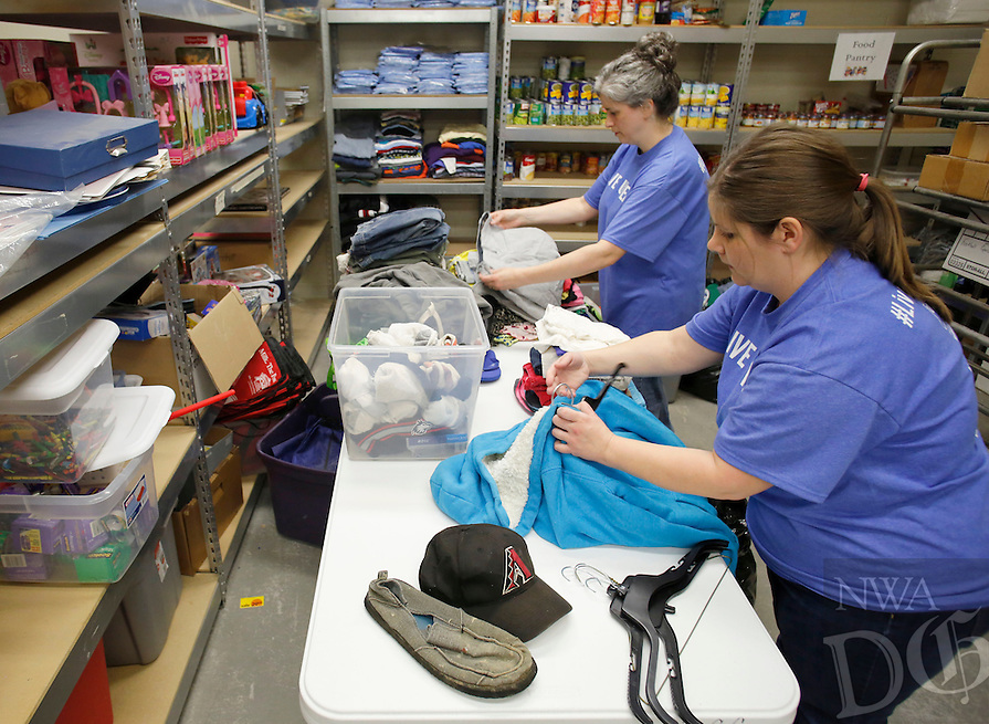 NWA Democrat-Gazette/DAVID GOTTSCHALK - 4/15/15 - Keri Lotz (right) and Angelia von Bose (cq), both with Harp's Food Stores Inc., organize clothing items in the storage room of the Donald W. Reynolds Boys and Girls Club Wednesday April 15, 2015 in Fayetteville. Local volunteers are paired with non-profits to complete much needed projects during Live United Day serving Benton, Madison and Washington Counties in Arkansas and McDonald County in Missouri.