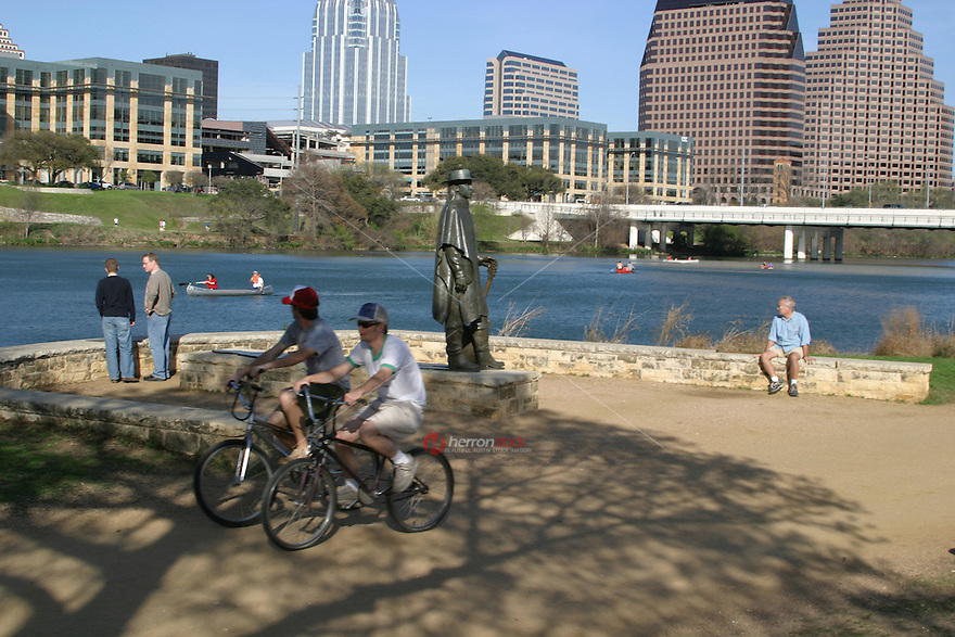 Bikers and tourist enjoy a beatiful Austin afternoon as the stroll past the SRV Memorial Statue on Town Lake.
