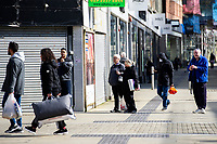 Pictured: A masked shopper in Swansea City Centre during the Covid-19 Coronavirus pandemic in Wales, UK, Swansea, Wales, UK. Monday 23 March 2020