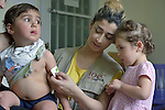 Maha Shoker, a health educator with International Orthodox Christian Charities, a member of the ACT Alliance, uses a mid-upper arm circumference (MUAC) measuring tape as she examines a Syrian refugee child in the community health center in Kab Elias, a town in Lebanon's Bekaa Valley which has filled with Syrian refugees. Another refugee child looks on. Lebanon hosts some 1.5 million refugees from Syria, yet allows no large camps to be established. So refugees have moved into poor neighborhoods or established small informal settlements in border areas. International Orthodox Christian Charities provides support for the community clinic in Kab Elias, which serves many of the refugees. <br /> <br /> PARENTAL CONSENT OBTAINED