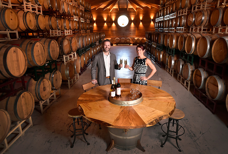 Artists Ryan Danger and Megan McSweeney-Troyer (Immersion Design)collaborated to create this one-of-a-kind table out of a wine barrel. They are photographed here with the finished wine barrel table in the same barrel room where the barrel came from.