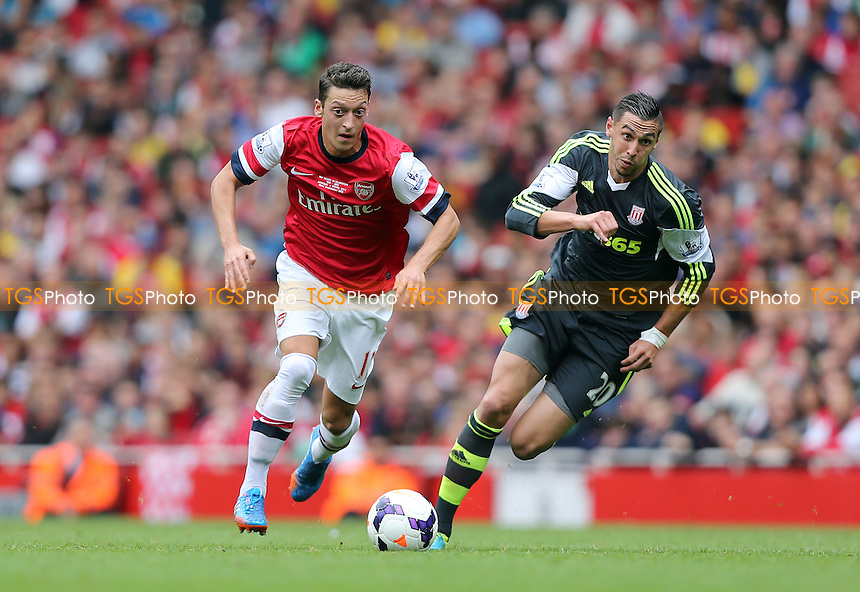 Mesut Ozil of Arsenal and Geoff Cameron of Stoke - Arsenal vs Stoke City, Barclays Premier League at the Emirates, Arsenal - 22/09/13 - MANDATORY CREDIT: Rob Newell/TGSPHOTO - Self billing applies where appropriate - 0845 094 6026 - contact@tgsphoto.co.uk - NO UNPAID USE