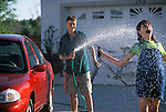 Brother spraying sister with water while washing car
