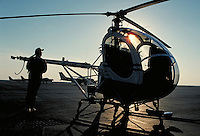 Pilot preparing the helicopter for takeoff silhouetted by the rising sun.  May not be used in an elementary school dictionary. Cleveland Ohio USA.