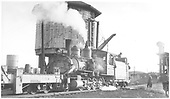 3/4 fireman's-side view of D&amp;RGW #268 w/dismantling train at Gunnison water tank coupled to the rail winch built on spreader OV's chassis.<br /> D&amp;RGW  Gunnison, CO  1955