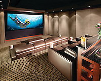 A beautiful theater with plush seating and a functional rear bar area for entertaining guests.  Hidden B&W speakers do not detract from the elegant acoustic panels that help the room sound as elegant as it looks.