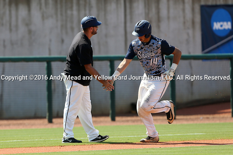 02 June 2016: Nova Southeastern's Jake Anchia (14) is greeted by head coach Greg Brown (left) as he rounds third base after hitting a home run. The Nova Southeastern University Sharks played the Cal Poly Pomona Broncos in Game 11 of the 2016 NCAA Division II College World Series  at Coleman Field at the USA Baseball National Training Complex in Cary, North Carolina. Nova Southeastern won the semifinal game 4-1 and advanced to the championship series.