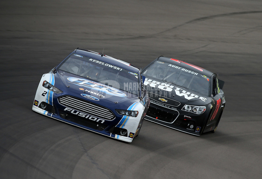 Mar. 3, 2013; Avondale, AZ, USA; NASCAR Sprint Cup Series driver Brad Keselowski leads Kurt Busch during the Subway Fresh Fit 500 at Phoenix International Raceway. Mandatory Credit: Mark J. Rebilas-
