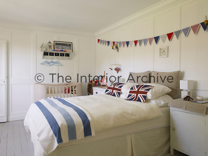 In this bedroom simple multi-coloured bunting stretched the length of a white-painted panelled wall creates a cheerful swathe of colour