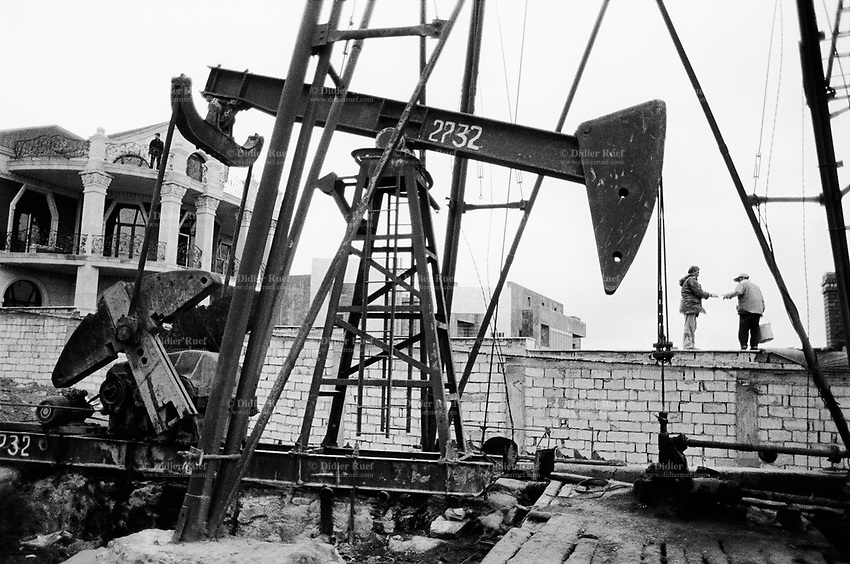 Azerbaijan. Baku Region. Baku. Two blue-collar workers stand on a bricks wall. Expensive private three flloors house on construction. Building site. State Oil Company of Azerbaijan Republic (SOCAR) is the project owner of the oil field. Oil-extracting infrastructure. Wells heads and nodding donkeys. Drilling derricks and rigs. Oil production. Ecological disaster and a source of pollution as a result of well water and oil spill discharge. © 2007 Didier Ruef