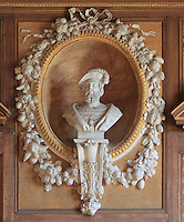 Bust of King Francois I in marble, 1835, by Achille Joseph Etienne Valois, 1785-1862, with gilded frame in carved stucco surrounded by fruit garland, in the Galerie Francois I, begun 1528, the first great gallery in France and the origination of the Renaissance style in France, Chateau de Fontainebleau, France. The Palace of Fontainebleau is one of the largest French royal palaces and was begun in the early 16th century for Francois I. It was listed as a UNESCO World Heritage Site in 1981. Picture by Manuel Cohen