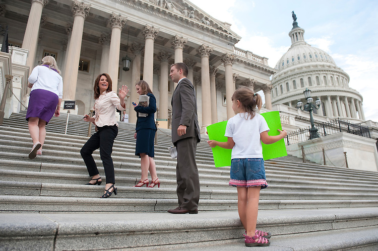 UNITED STATES - AUGUST 1: Presidential candidate Rep. Michele Bachmann, R-Minn., waves to Jubilee Matthews and her family from Kansas City, Mo., as they hold a family protest calling for a balanced budget at the House steps during the vote on the debt ceiling bill in the House of Representatives on Monday, Aug. 1, 2011. (Photo By Bill Clark/Roll Call)