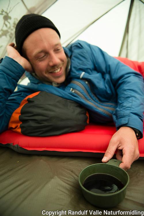 Mann drikker kaffe i telt. ---- Man drinking coffe in tent.