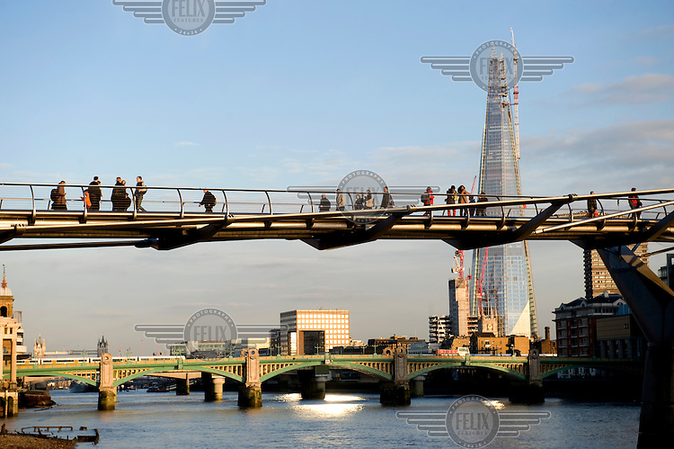 Pedestrians cross the Millennium Bridge that connects the south and north banks of the River Thames in London. To the right is the almost completed Shard (310 metres).