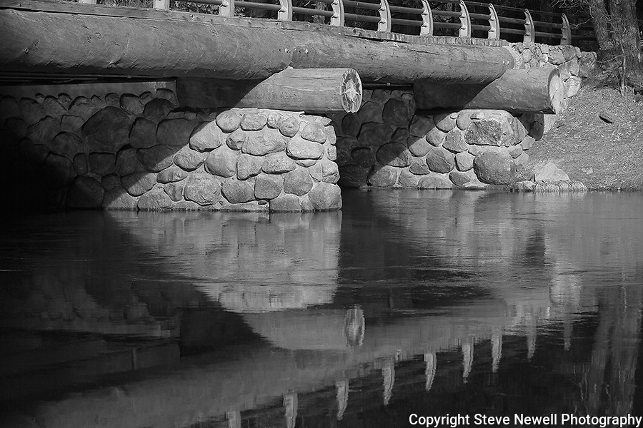 """Yosemite Bridge"" Black and White. Yosemite National Park, California.  The Merced River running under a bridge on the park's valley floor near the El Capitan rock formation."