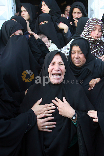 Palestinian relatives of Hisham Ghalban mourn during his funeral in Khan Younis in the southern Gaza Strip, on November 15, 2012. Tensions between Israel and Gaza have sparked a furious response from Egypt's Islamist administration, which has close ties with the Palestinian territory's ruling Hamas movement, with Cairo recalling its ambassador in protest at Israel's killing of head of the Ezzedin Qassam Brigades, Ahmad Jaabari, on November 14. Photo by Eyad Al Baba