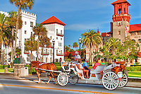 A horse and carriage travels down King Street in historic downtown St. Augustine, Florida. In the background there is the St. Augstine City Hall/Lightner Mueeum building and the Casa Monica Hotel.