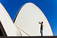A woman photographs the Sydney Opera House.  Sydney, New South Wales, AUSTRALIA.