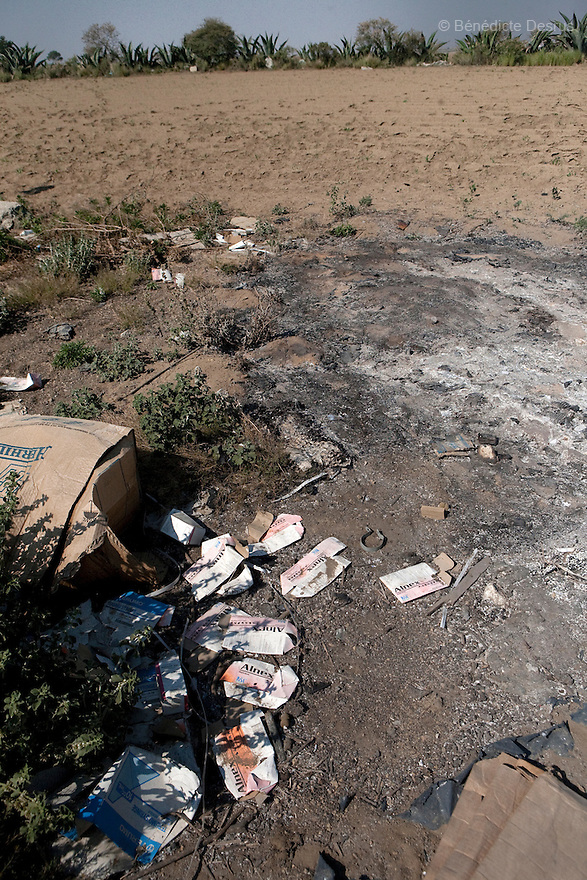 "3 may 2009 - Mexico - Used swine medication and material burnt by a Carrol Farm employee in the village of Loma Larga located near Perote,Veracruz. Located in the states of Veracruz and Puebla, near Mexico City, Granjas Carroll is an industrial pig farms that produces close to 1 million animals a year. It is 50% owned by US company Smithfield Foods, the world´s largest producer and processor of pork products. In La Gloria, near where the farms are located, residents have been complaining about manure dumps, flies and smell from the farms for a long time. Since February, they have warned the authorities that the wastes of these pig breeding farms caused an outbreak of respiratory infections and pneumonia in 60% of their 3000 inhabitants. Mexican media has called the Carrol pig farms ""ground zero"" for infection. It recently was confirmed that an influenza case in the city, reported two weeks before the cases in Mexico City, was in fact the new strain of H1N1, combining genetic material from avian, swine and human influenza. The Food and Agriculture Organization (FAO) says that so far there is no established evidence that this strain of the influenza A virus has entered the human population directly from pigs, but it urges national governments and the international community to step up disease surveillance in swine. FAO together with the World Organization for Animal Health (OIE), will send a team of experts to Mexico this week to help the government assess the epidemiologic situation in the pig production sector. A spokesperson from Smithfields Foods said there is no clinical signs of influenza being reported in pigs or employees in the farm. Photo credit: Benedicte Desrus / Sipa Press"